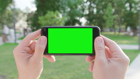 Two hands holding a phone with a green screen in a horizontal position in a public park. Close-up shot. Soft focus 免版税图像