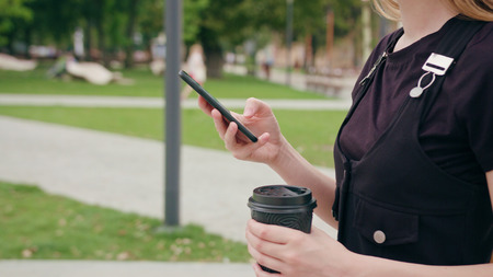An attractive young red-haired ladywalking and using a phone in town. Close-up dolly shot. Soft focus on the phone and cup