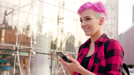A young woman with a pink short hair using a phone in the city street. Close-up shot. Soft focus. Dolly shot. Archivio Fotografico