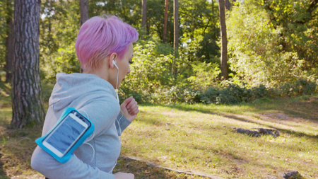 A young y with pink hair jogging in the forest. Medium shot Stock Photo
