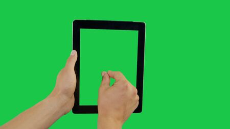 Pointing Finger Zoom Out On Device Screen with Green Background. Digital Tablet Green Screen. Use in any project that depicts finger, gesture, touchscreen and the like. Stockfoto