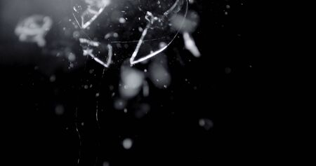 Shattered and broken glass shards flying through the air after crush broken window on a black background