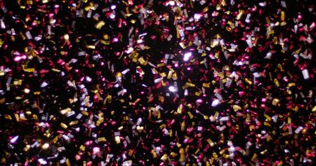 Confetti fired in the air during a party. Only confetti on black background of the night. Falling metallic glitter foil confetti multicolor in black background. 版權商用圖片