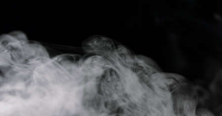 swirling white cloud of smoke against a black 免版税图像