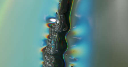 Forming Bubbles In Metallic Sheet. Metallic sheet being depressed onto a surface, forming bubbles and a rainbow gloss as it shines in the light.