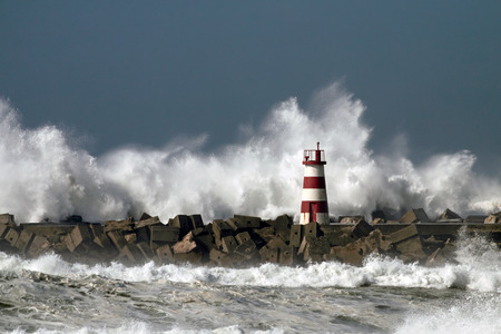 stormy: Storm waves over beacon of the harbor of Povoa do Varzim, Portugal Stock Photo