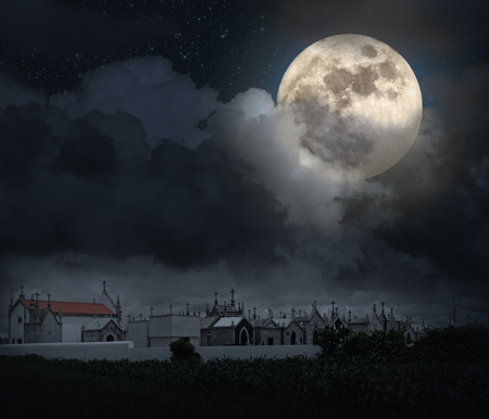 Halloween scenery with full moon, cloudy sky, and old European cemetery (digital grain added) Stock Photo