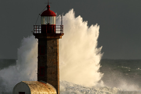 lighthouse: Storm waves over lighthouse of the harbor  of river Douro, Portugal; end of the day light. Stock Photo