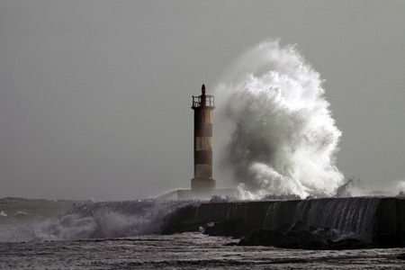 Big wave against lighthouse in the north of Portugal photo