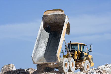 Heavy dump truck against blue sky operating in a marble quarry photo