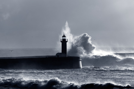 Backlit dramatic big wave over lighthouse. Toned blue. photo