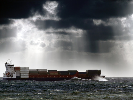 Commercial Ship crossing ocean in a stormy sunset with sun beams; enhanced sky Archivio Fotografico