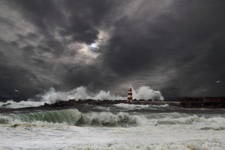 Storm waves over beacon of the harbor of Povoa do Varzim, Portugal - enhanced sky