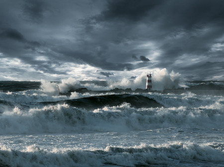 Waves over a lighthouse against stormy clouds. Enhanced sky. Toned blue.