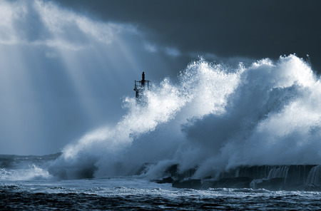 storm: Big ocean wave over lighthouse against dramatic enhanced sky with sunbeams. Toned blue. North of Portugal. Stock Photo