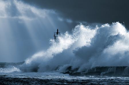 Ola oceánica grande sobre el faro contra el cielo dramático con rayos de sol mayor. Tonos de azul. Norte de Portugal. Foto de archivo