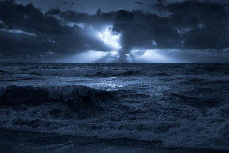 nocturnal: Nocturnal photo composition with moon, clouds, light beams, sea and waves