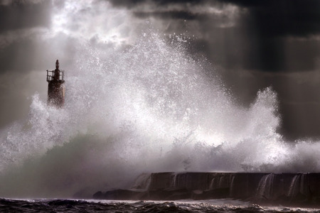 lighthouse with beam: Big storm wave against lighthouse of Vila do Conde, north of Portugal (enhanced sky) Stock Photo