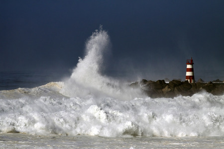 Storm waves over beacon of the harbor of Povoa do Varzim, Portugal Stock Photo