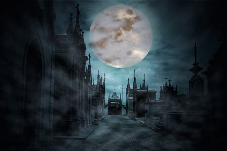 Main street of an old European cemetery in a cloudy and foggy full moon night photo