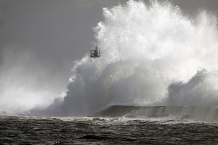 Big wave against lighthouse in the north of Portugal in a stormy overcast evening - mouth of river Ave in Vila do Conde Archivio Fotografico