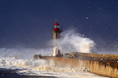 Lighthouse under heavy storm seeing waves foam in the air carried by the strong wind