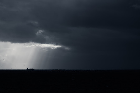 Dark minimalist seascape with silhouette of a commercial ship, overcast sky, sunbeams and black sparkling sea photo