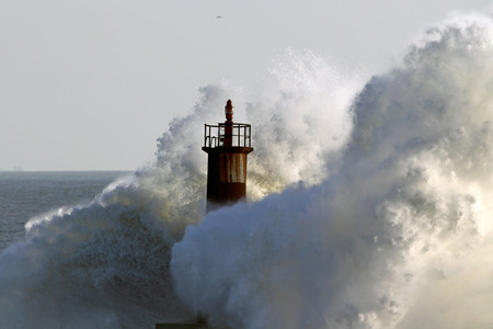 storm tide: Big wave against lighthouse in the north of Portugal in a stormy overcast evening - mouth of river Ave in Vila do Conde Stock Photo