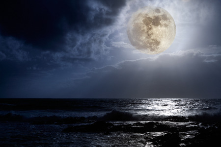 Nocturnal photo composition with moon, clouds, light beams, sea and waves
