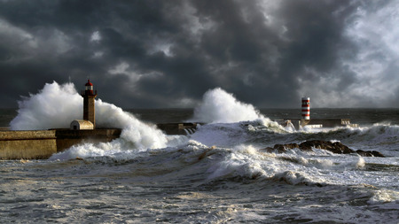 Stormy sunset at the harbor of the mouth of the river Douro, in Porto, Portugal, with big waves against old lightouse, new pier and beacon; enhanced sky Archivio Fotografico