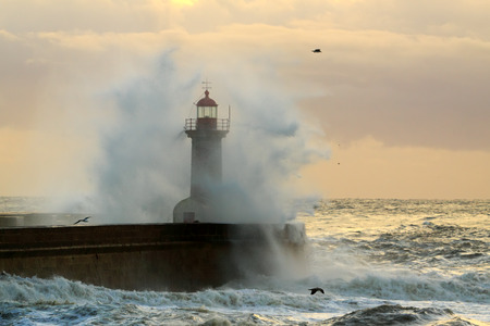 Old lighthouse of the entry of the harbor of river Douro during a winter storm sunset