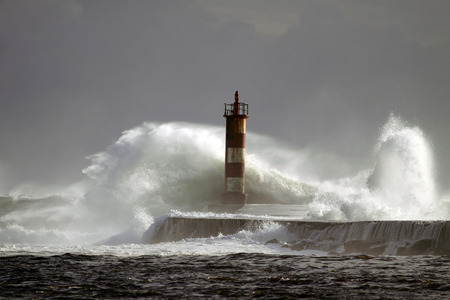 Big wave against lighthouse and pier in the north of Portugal in a stormy overcast evening - mouth of river Ave in Vila do Conde, near Porto Archivio Fotografico