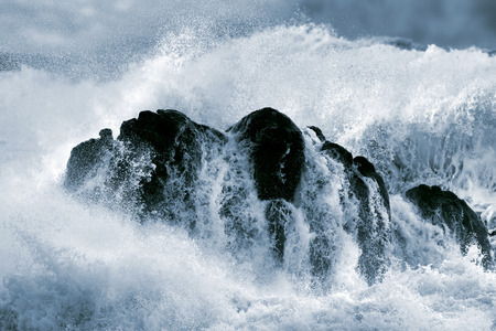 large rock: Detailed photo of a big stormy wave crashing over a boulder