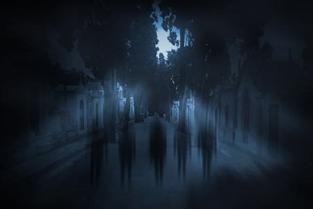 Ghosts passing on the main street of an old european cemetery on a foggy full moon night