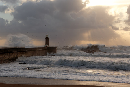 Beautiful winter seascape at sunset  with big waves over pier and lighthouse, Porto, Portugal photo