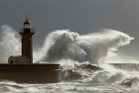 storm tide: Big stormy waves against lighthouse with interesting light. Porto, Portugal.  Low edition photo. Stock Photo