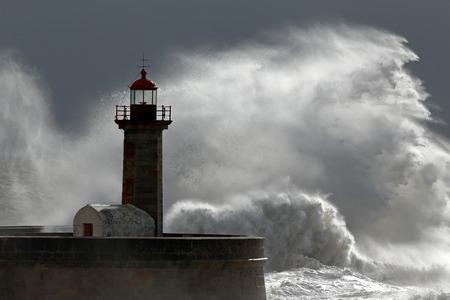 Huge wave over old lighthouse of Porto, Portugal photo