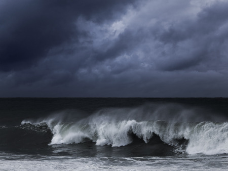 Big wave against dark dramatic enhanced sky. Toned blue. Stock Photo