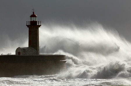 windy energy: Huge windy wave against lighthouse Stock Photo