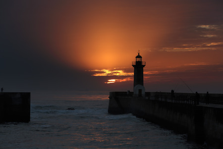 Beautiful sunset on the old pier and lighthouse at the mouth of the river Douro, Porto, Portugal photo