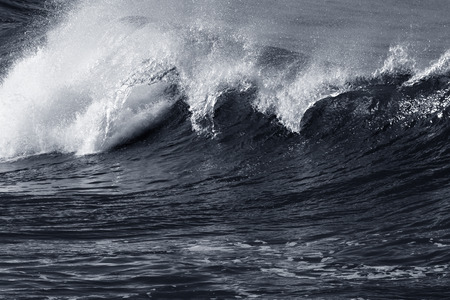 tsunami wave: Big breaking wavein a stormy but sunny morning. Black and white toned blue.