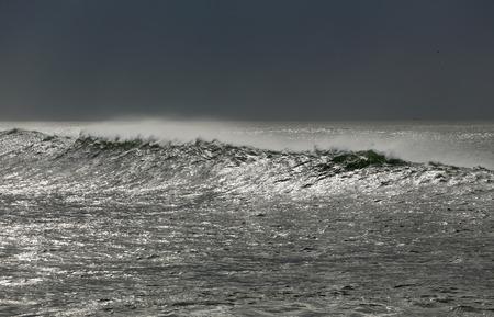 glistening: Larga ola acercarse a la costa en un mar reluciente Foto de archivo