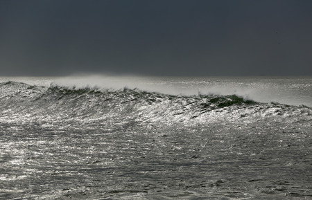 glistening: Long wave approaching the coast in a glistening sea Stock Photo
