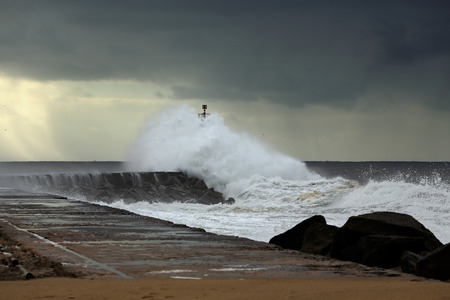 Wave over pier and beacon of Ave river mouth, north of Portugal, before rain and big storm