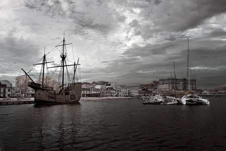 conde: Vila do Conde, Portugal - September 12, 2014: Replica of a boat from the time of discovery, caravel, anchored at the mouth of the river Ave, medieval town of Vila do Conde, where part of these boats were built. Infrared filter has been used. Editorial