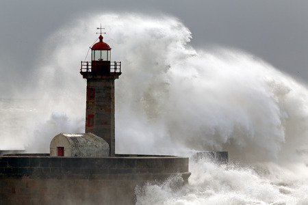 Big wave over old lighthouse and pier, Porto, Portugal