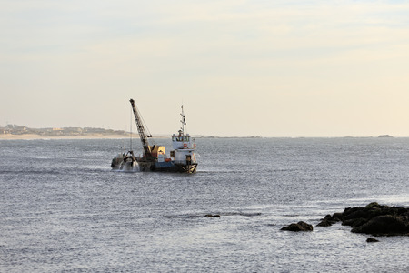 crane bucket: Small dredge operating in the dredging of the river mouth Ave, Porto, Portugal