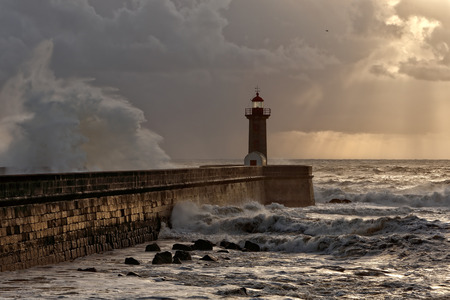 Stormy sunset with big wave over pier and sunbeams, Porto, Portugal Stock Photo