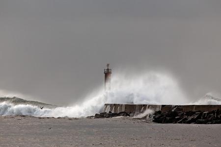 hurricane weather: Big waves over lighthouse. Vila do Conde, Portugal.