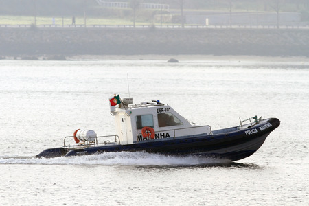law of portugal: Porto, Portugal - January 2, 2013: Police maritime boat during normal surveillance on Douro River in a foggy morning